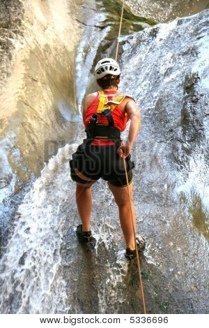 Woman Climbing A Waterfall