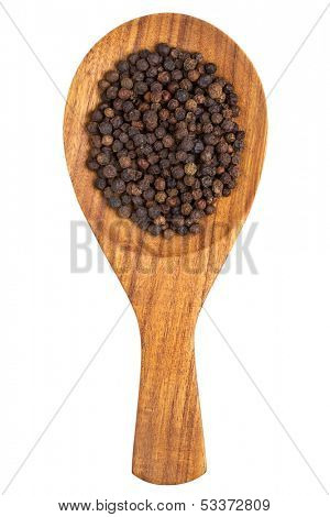 Black pepper (Piper nigrum) peppercorns in the wooden spoon on white background