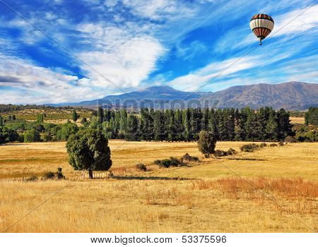 Picturesque field after harvesting at sunset. A field of yellow grass demarcated green alleys. Flies over a field of multi-colored balloon