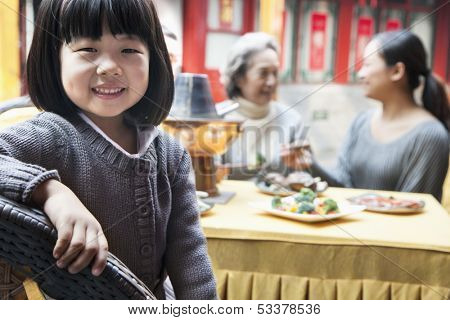 Portrait of young girl at family meal