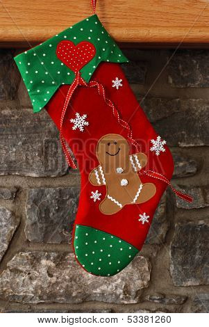 Christmas stocking (with smiling gingerbread man holding a heart shaped balloon) hanging from mantel of stone fireplace.  Stocking is an original design created and handcrafted by me.