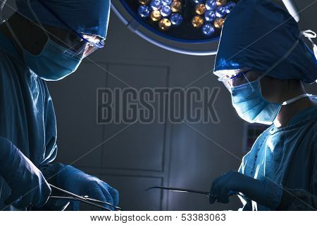 Two surgeons looking down and working at operating table