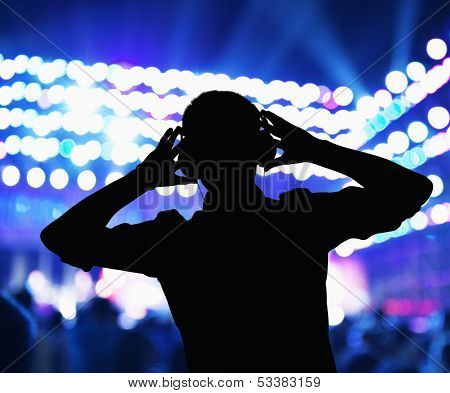 Silhouette of DJ wearing headphones and performing at night club
