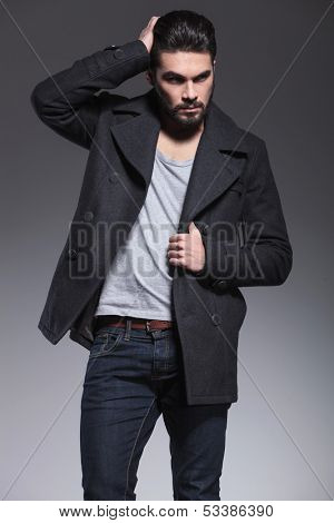 young bearded man passing his hand through his hair and looks away from the camera