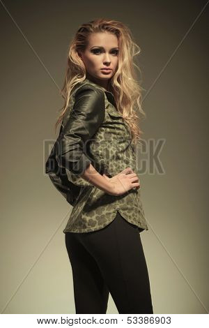 side view of a young sexy blonde woman in leather pants posing with her hands on hips