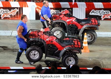 MOSCOW - MAR 02: Strong men raise ATVs on the festival extreme sports Breakthrough 2013 in the arena of the Olympic Sports Complex, on March 02, 2013 in Moscow, Russia.