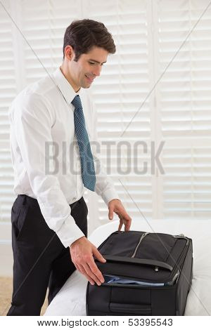 Side view of a smiling businessman unpacking luggage at a hotel bedroom