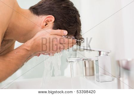 Side view of a shirtless young man washing face in the bathroom