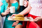 Friends or couple eating fast food for breakfast with pancakes and coffee in American fast food dine