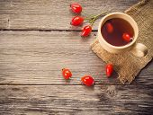 stock photo of home remedy  - cup of tea with hip roses on wooden table - JPG