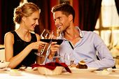stock photo of positive  - Beautiful young couple with glasses of red wine in luxury restaurant - JPG