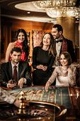 picture of roulette table  - Group of young people behind roulette table in a casino - JPG