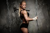 Beautiful muscular bodybuilder woman holding hammer and chains