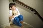 stock photo of staircases  - A sad and depressed boy is sitting in the corner of a staircase - JPG