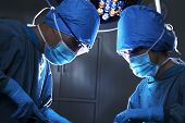 foto of hospital gown  - Two surgeons working and concentrating at operating table - JPG
