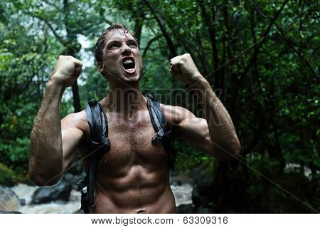 Muscular survivor man in jungle rainforest cheering aggressive. Strong male survival concept with guy celebrating cheerful in forest at night showing muscles and aggressive survival instincts.