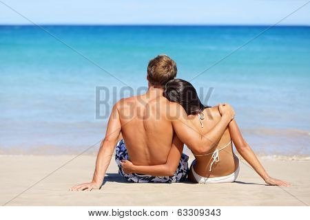 Romantic beach couple in love relaxing on vacation enjoying ocean view together sitting in the sand embracing and hugging. Beautiful young multiracial couple, Asian woman, Caucasian man.