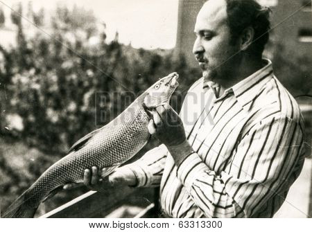 Vintage photo of man holding caught fish (1970's)
