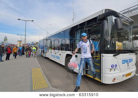 SOCHI, RUSSIA - FEBRUARY 14, 2014: Fan exiting the bus arrived from Sochi to Adler during XXII Winter Olympics. Bus service between Olympic venues is free of charge during Olympic Games