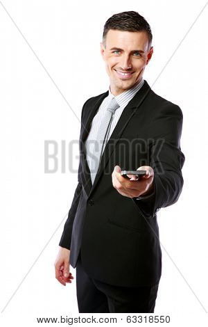 Smiling businessman in a suit giving you a smartphone over white background