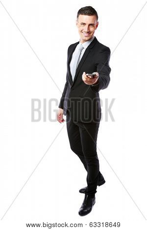 Happy businessman in a suit giving you a smartphone over white background