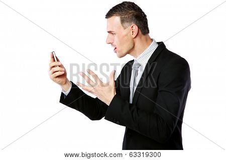 Angry businessman yelling on his cell phone over white background