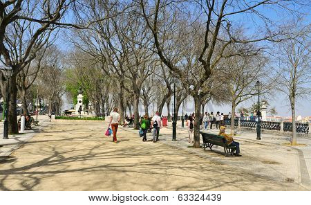 LISBON, PORTUGAL - MARCH 17: People walking in Jardim de Sao Pedro de Alcantara on March 17, 2014 in Lisbon, Portugal. There is a panoramic view of the city from this public park