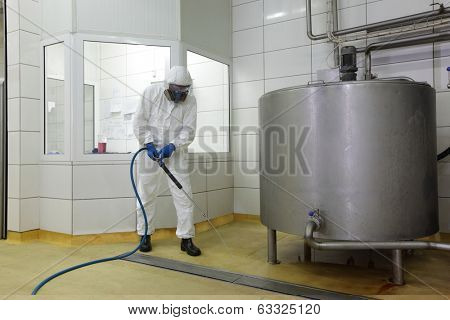 worker in white protective uniform,mask,gloves  with high pressure washer at  large industrial process tank  cleaning floor  in plant
