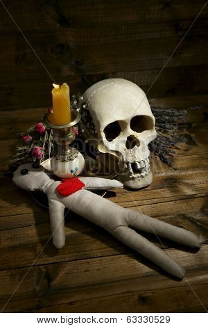 Conceptual photo of love magic. Composition with skull, voodoo doll, dried herbs and candle on  dark wooden background
