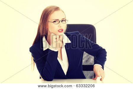 Attractive business woman by the table, bossy behaviour. Isolated on white.