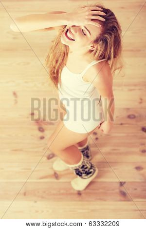 Cheerful, carefree young caucasian woman feels happy. Standing, or dacing, posing over wooden floor.