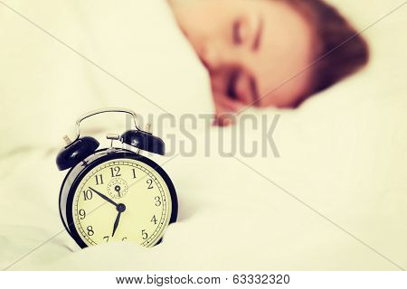 Beautiful sleeping woman with alarm clock. Focus on clock.