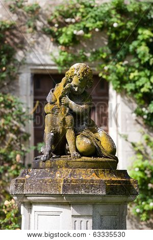 The sculpture of the child with the dog in the garden of the castle in Montresor