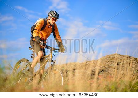 Cyclist Riding the Bike on the Beautiful Autumn Mountain Trail