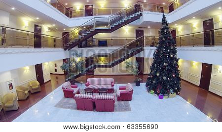 Atrium with armchairs, couches and Christmas tree in hotel. Aerial view