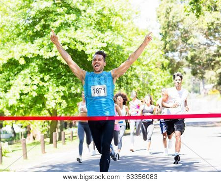 Excited male runner crossing the finshline of a marathon