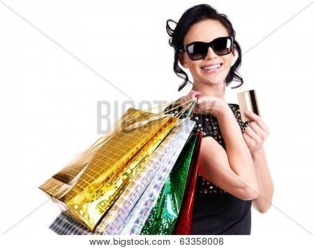 Happy woman in glasses with purchasing and credit card over white background.