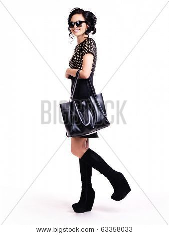 The beautiful fashionable young woman in black dress and glasses - isolated on white.