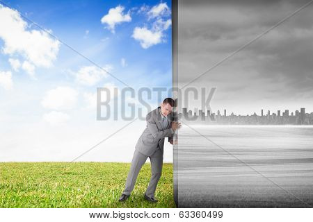 Composite image of businessman pushing away scene of field with tree and city on the horizon