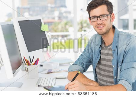 Portrait of a casual male photo editor using graphics tablet in a bright office