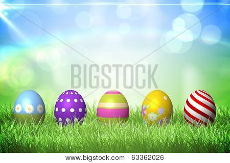 Colourful easter eggs on the grass under sunny sky