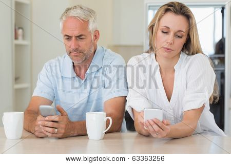Bored couple sitting at the counter texting at home in the kitchen