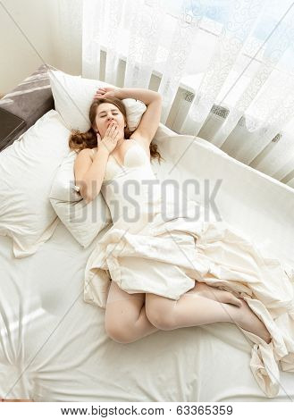 Woman In Lingerie Yawning At Morning In Bed