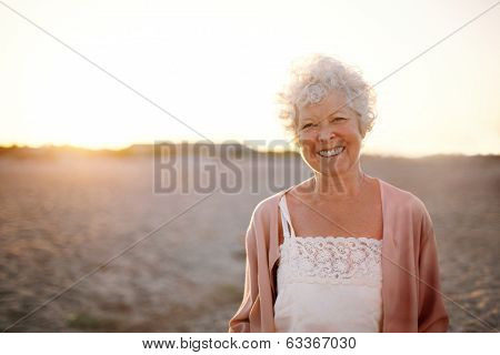 Cheerful Old Woman Standing On The Beach