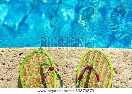 Two Flip Flops On The Platform Beside Swimming Pool