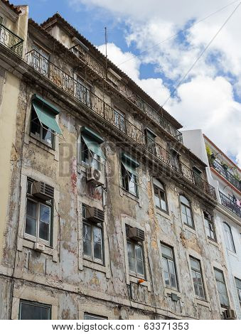 Old dilapidated house against the sky and clouds on the street of Lisbon, Portugal