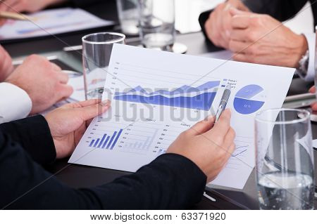 Businessman Holding Pen Over Graph In Business Meeting