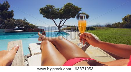 Woman Sunbathing Along A Pool With Orange Juice