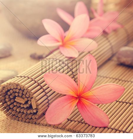 Health spa setting, low light with ambient. Frangipani, hot and cold stone on bamboo mat in vintage retro style.