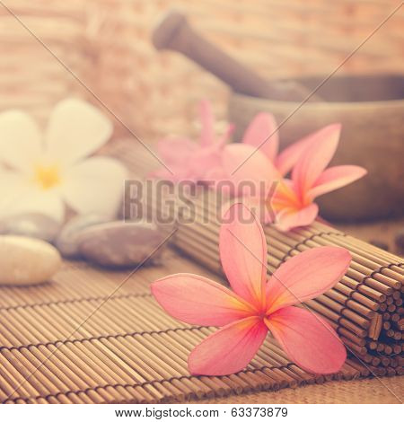 Spa setting, low light with ambient in vintage revival tone. Frangipani, hot and cold stone on bamboo mat.